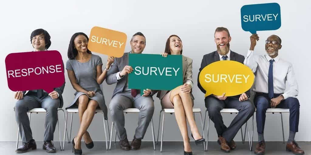 stock image of several people holding signs for a survey
