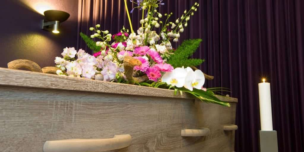 coffin with pink and white flowers at a funeral home