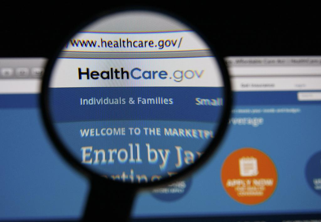 Photo of HealthCare.gov homepage on a monitor screen through a magnifying glass