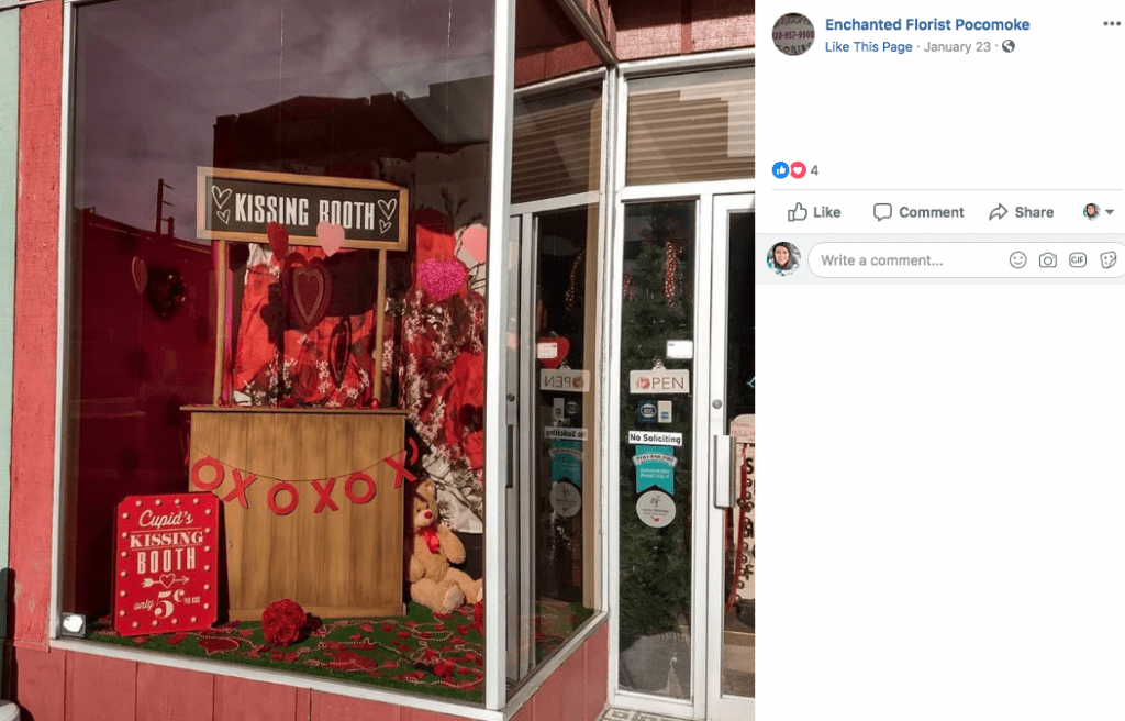 Lured by a window display with a kissing booth, couples in Pocomoke City, Maryland, have been stopping in Enchanted Florist to take a photo and place their Valentine's Day order.
