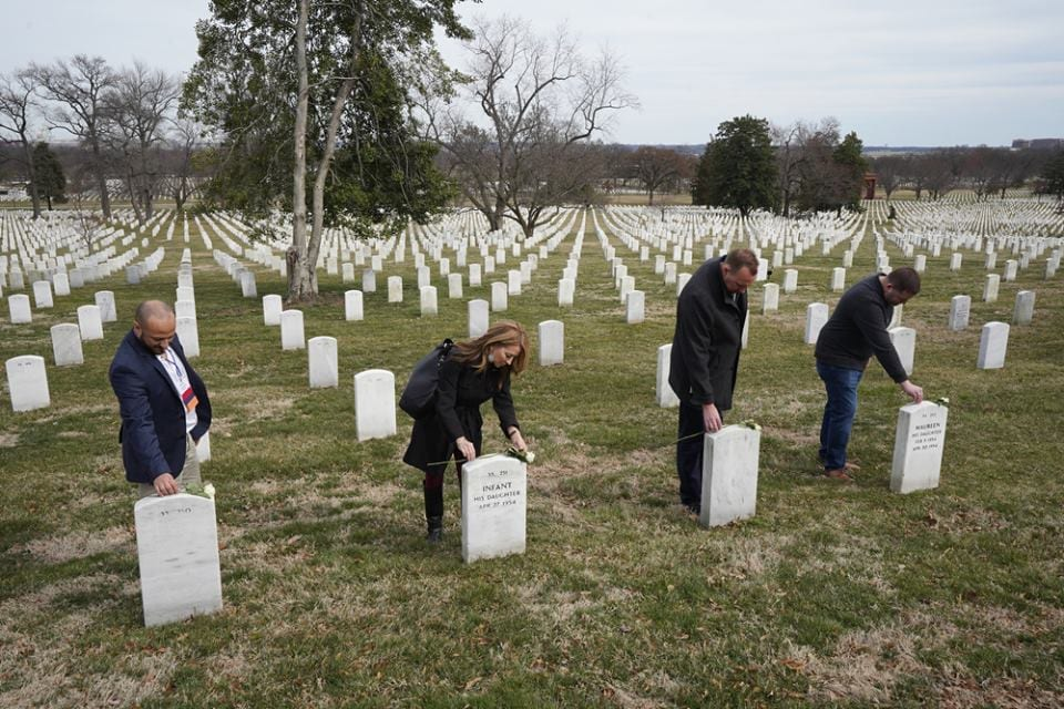 CAD participants pay their respects and place flowers on headstones during a visit to Arlington National Cemetery.