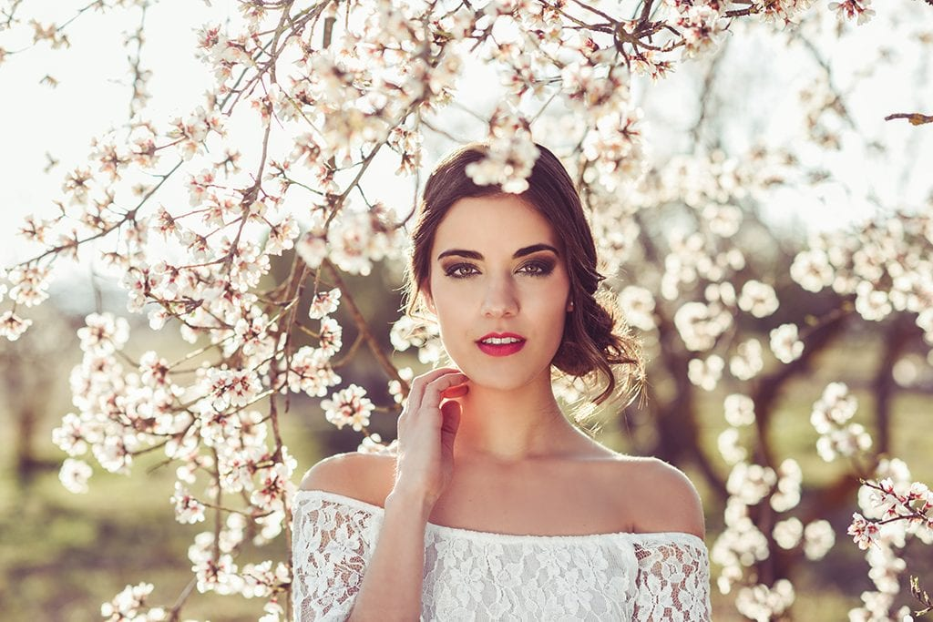 Portrait of young woman in the flowered garden in the spring time. Almond flowers blossoms