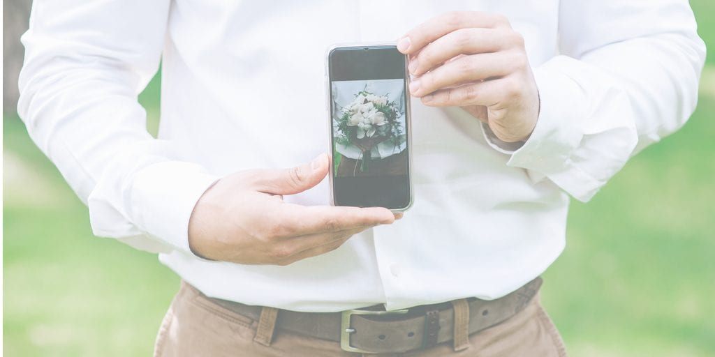 photo wedding bouquet on the phone in the hands of groom